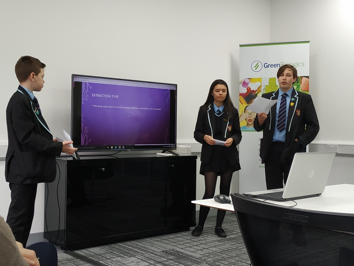 Three students in blazers presenting in front of others