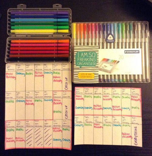 Colourful student revision timetables next to coloured fineliners on a black desk