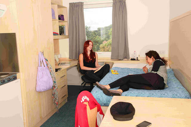 Two students sitting in a bedroom in Birks Grange Village at the University of Exeter