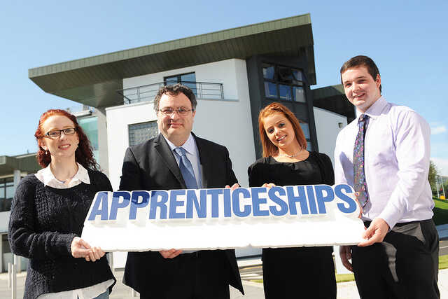 Four people holding up the word Apprenticeships in front of a college building