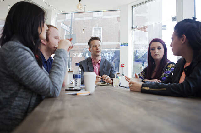 People sitting round a table in a cafe having a meeting