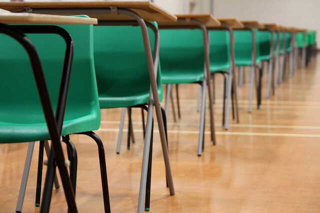 Exam hall with rows of tables and green chairs
