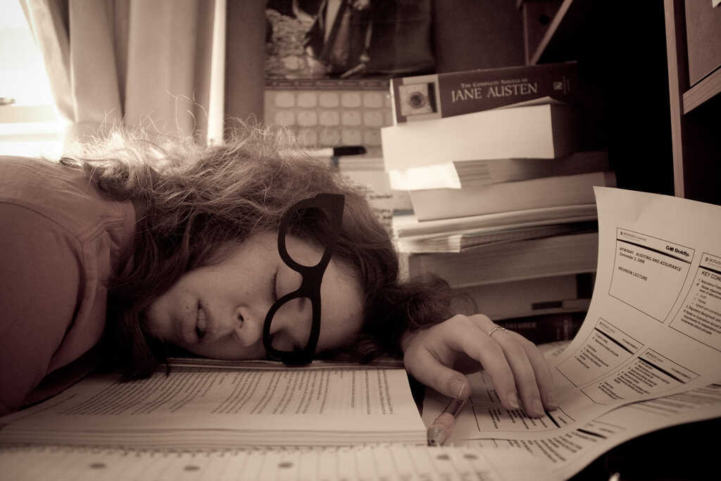 Black and white image of a young woman fallen asleep on her desk surrounded by books and notes