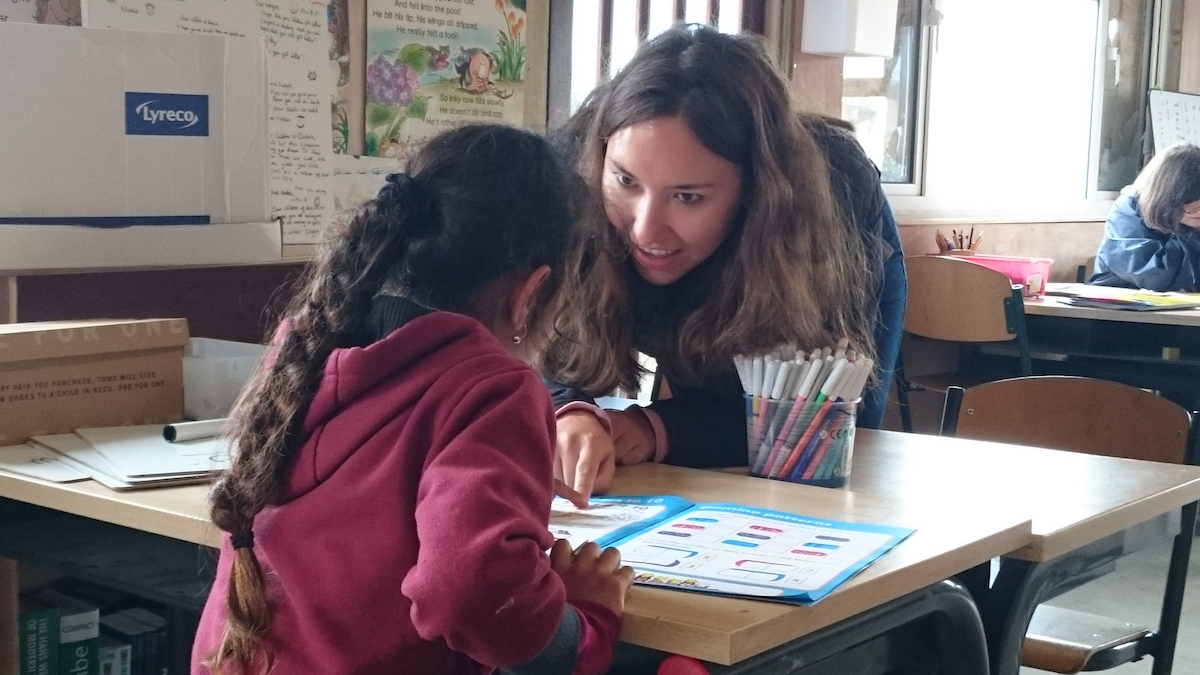 Female leaning over a school desk engaging with a primary school refugee