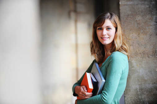 Young female holding books outside a university building