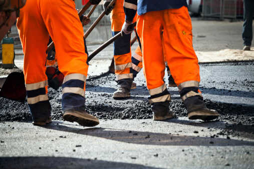 Workmen tarmacing a road in orage hi vis trousers