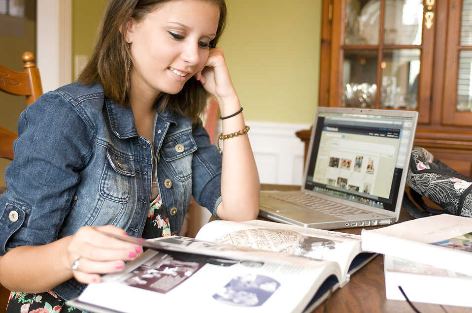Female student sitting at a dining room table looking at her book and laptop