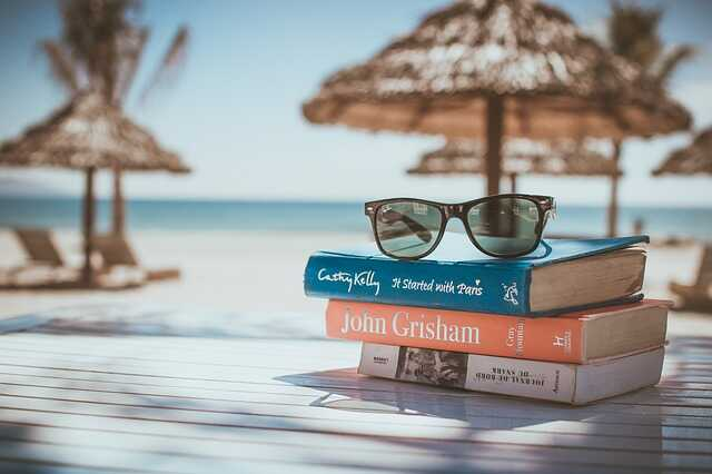 A pile of three books and a pile of sunglasses on a table with the beach in the background