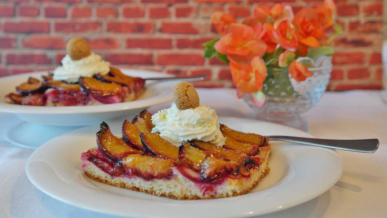 Table arranged with two plates of peach tarts topped with squirty cream and a biscotti biscuit