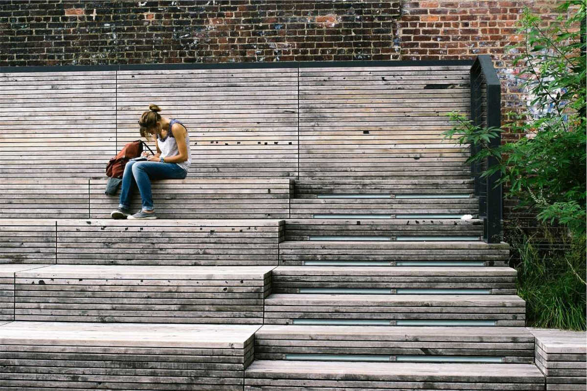 Young woman with a backpack writing in a notebook sitting on wooden steps