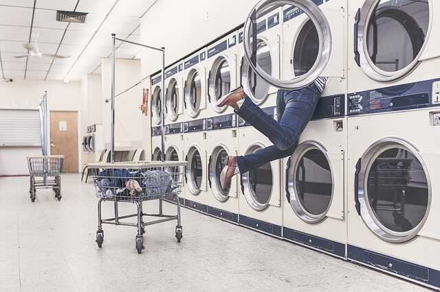 Person with head in washing machine at laundrette