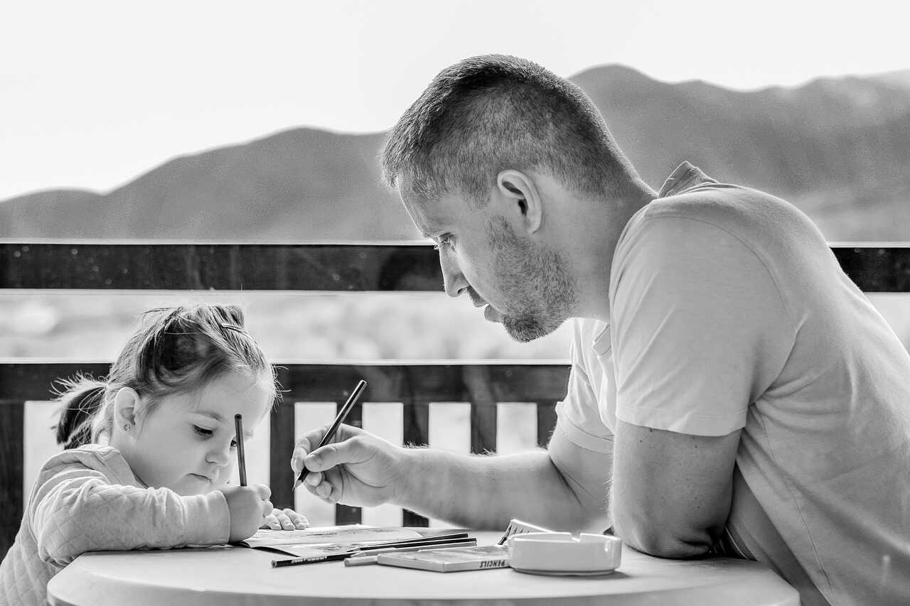 Black and white image of father and daugter colouring in