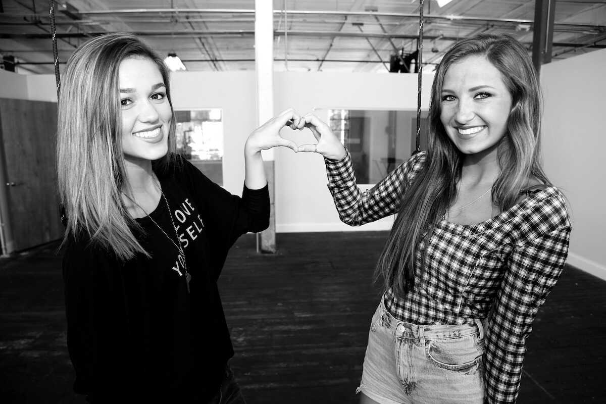 Black and white image of two young women creating a heart with their hands