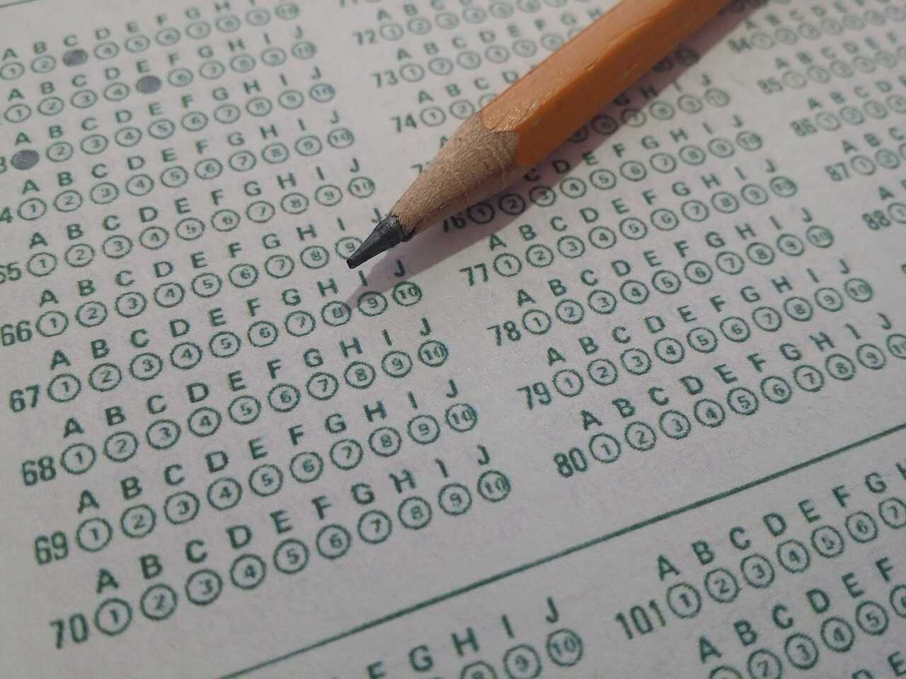 An orange pencil on a multiple choice answer sheet