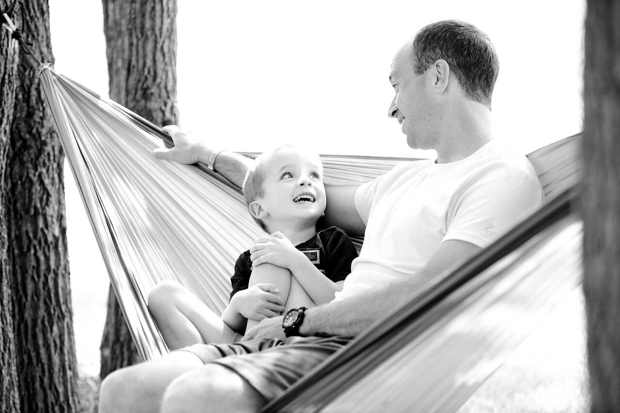 Black and white image of a father and his son sitting in a hammock