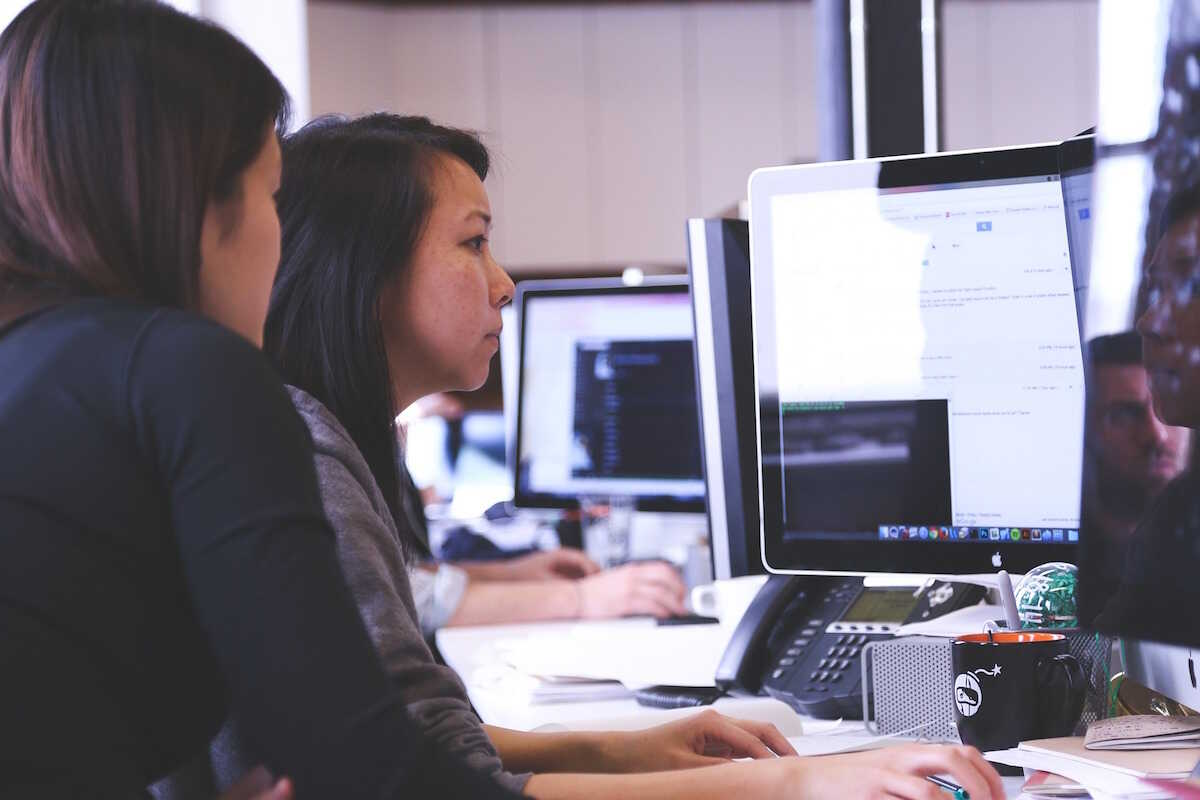 Two young women looking at a computer screen in an office