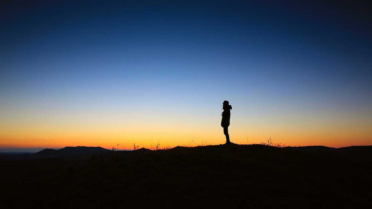 Silhouette of a person looking out over a sunset in the countryside