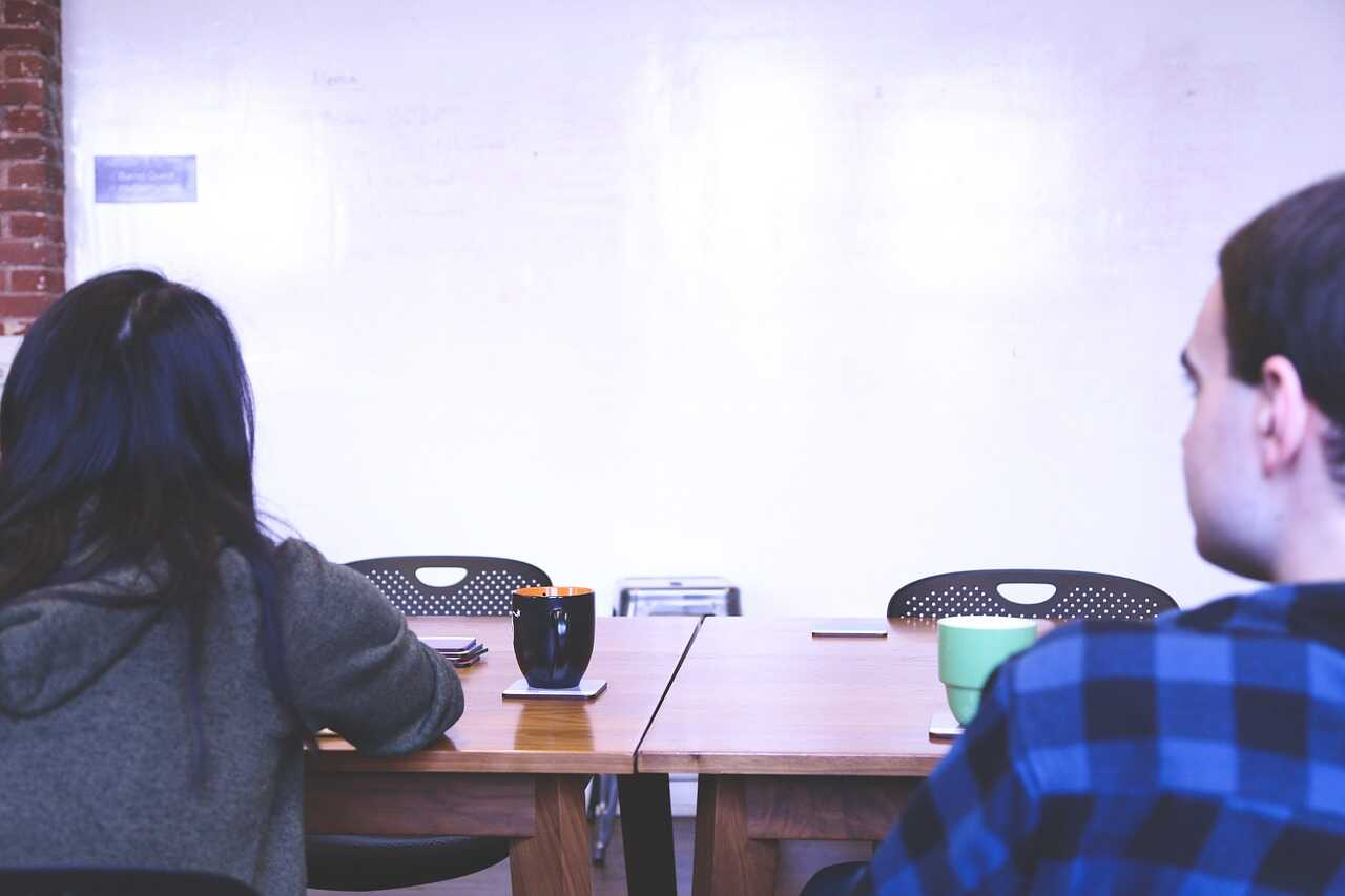 Two students facing a whiteboard across a meeting room table
