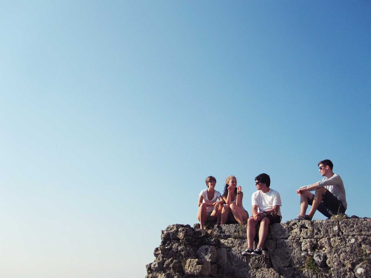 Young people sitting on a wall on a sunny day