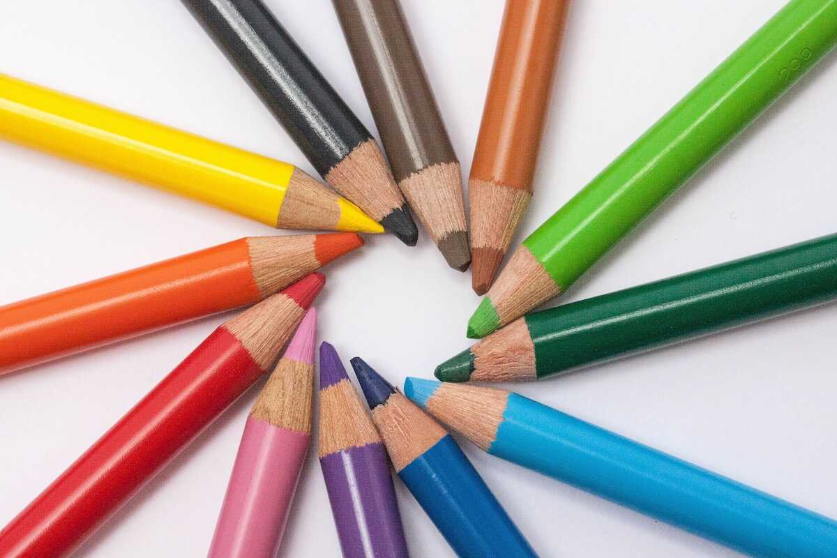 Multi-coloured pencils arranged in a circle on a white background