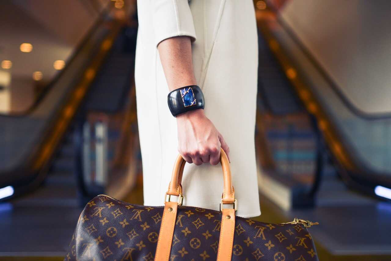 Woman in a white coat holding a Louis Vuitton overnight bag