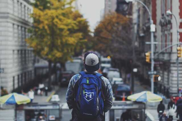 Student with a backpack looking over the street