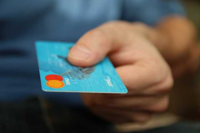 Hand holding out a blue debit card