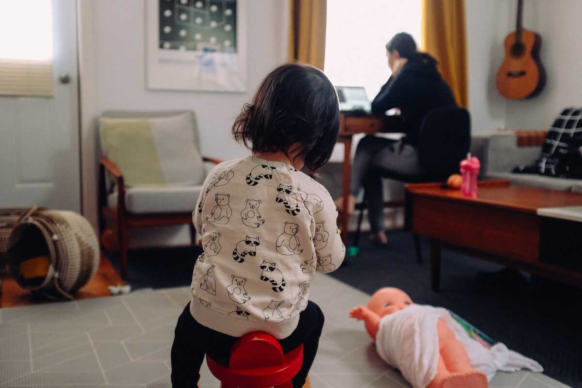 Toddler sitting on a stool while her mother works in the background