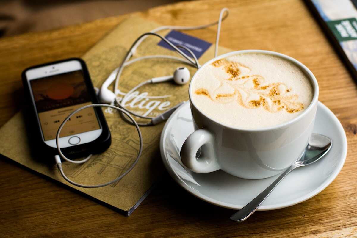 Coffee shop table featuring a milky coffee, phone playing music and headphones