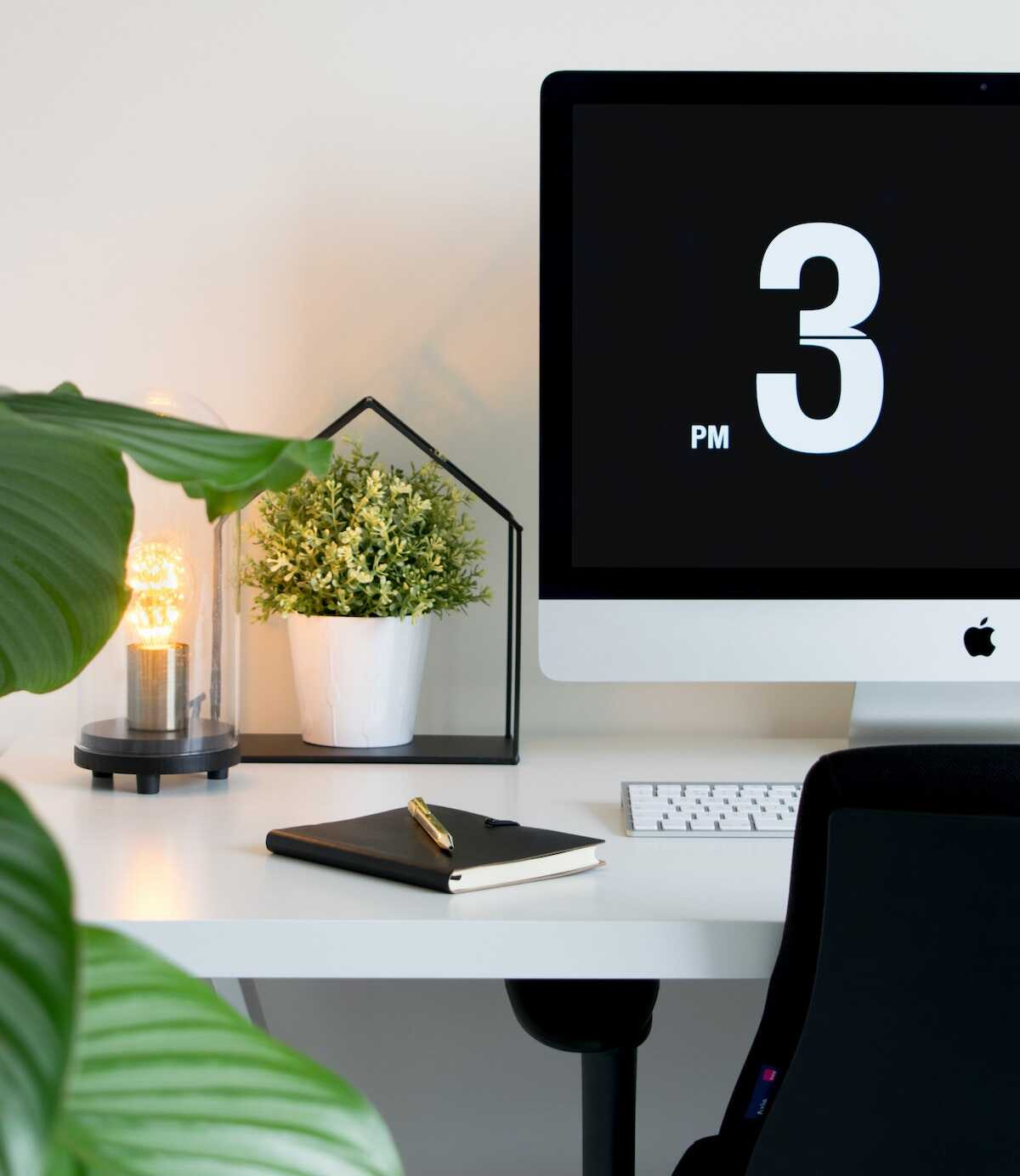 Home office desk featuring an Apple iMac