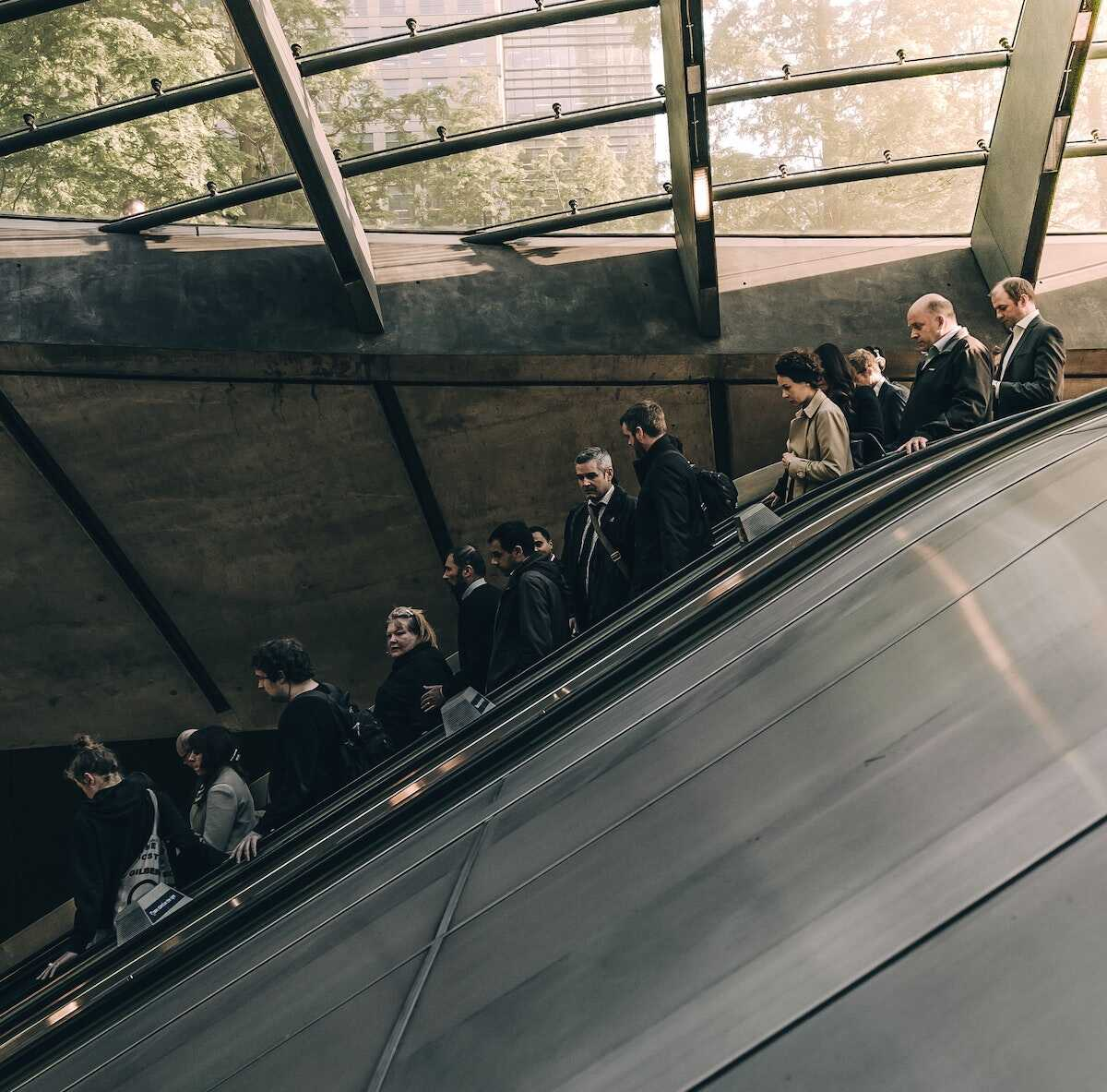 A London escalator at rush hour with lots of commuters
