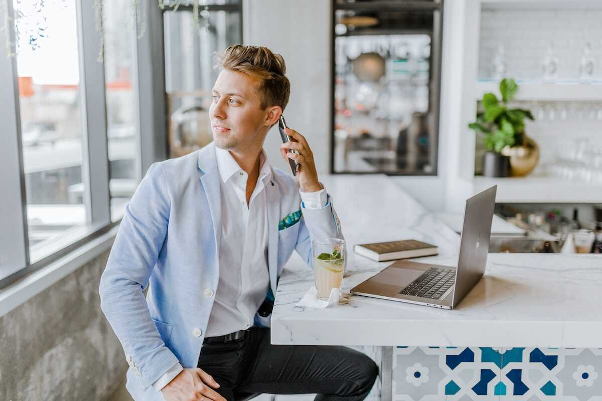 Professional man sitting in a cafe in front of a laptop speaking on the phone