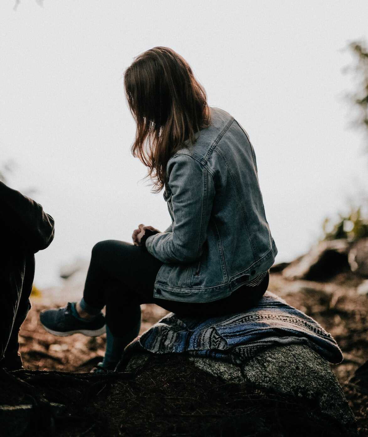 Woman sitting on a rock talking to her friend