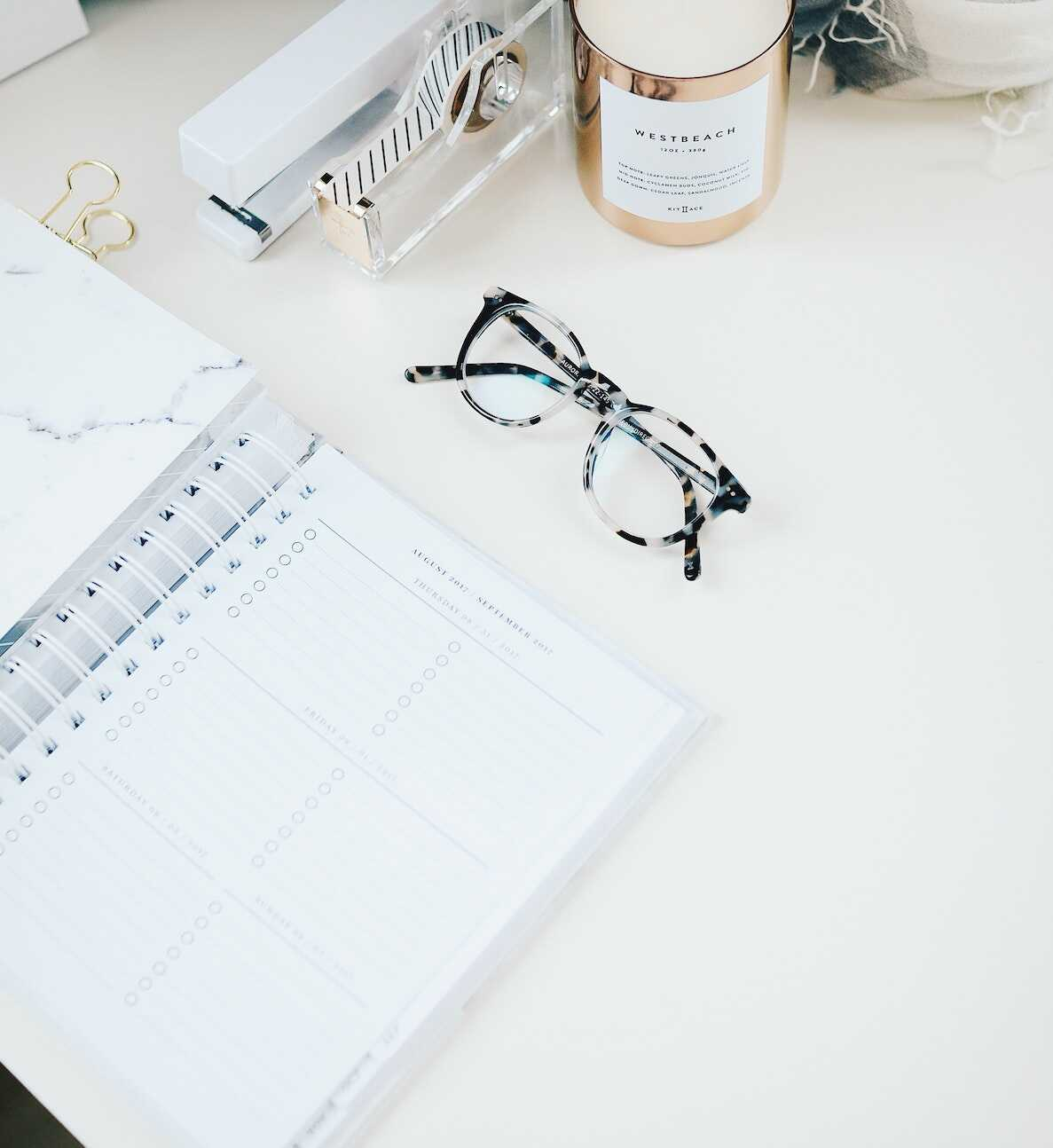 Home office desk featuring a diary, glasses, candle, stapler and washi tape