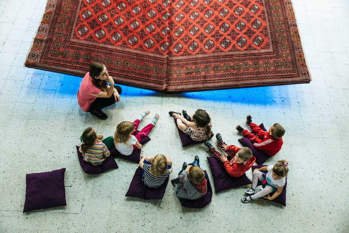 Children sitting on the floor listening to their teacher
