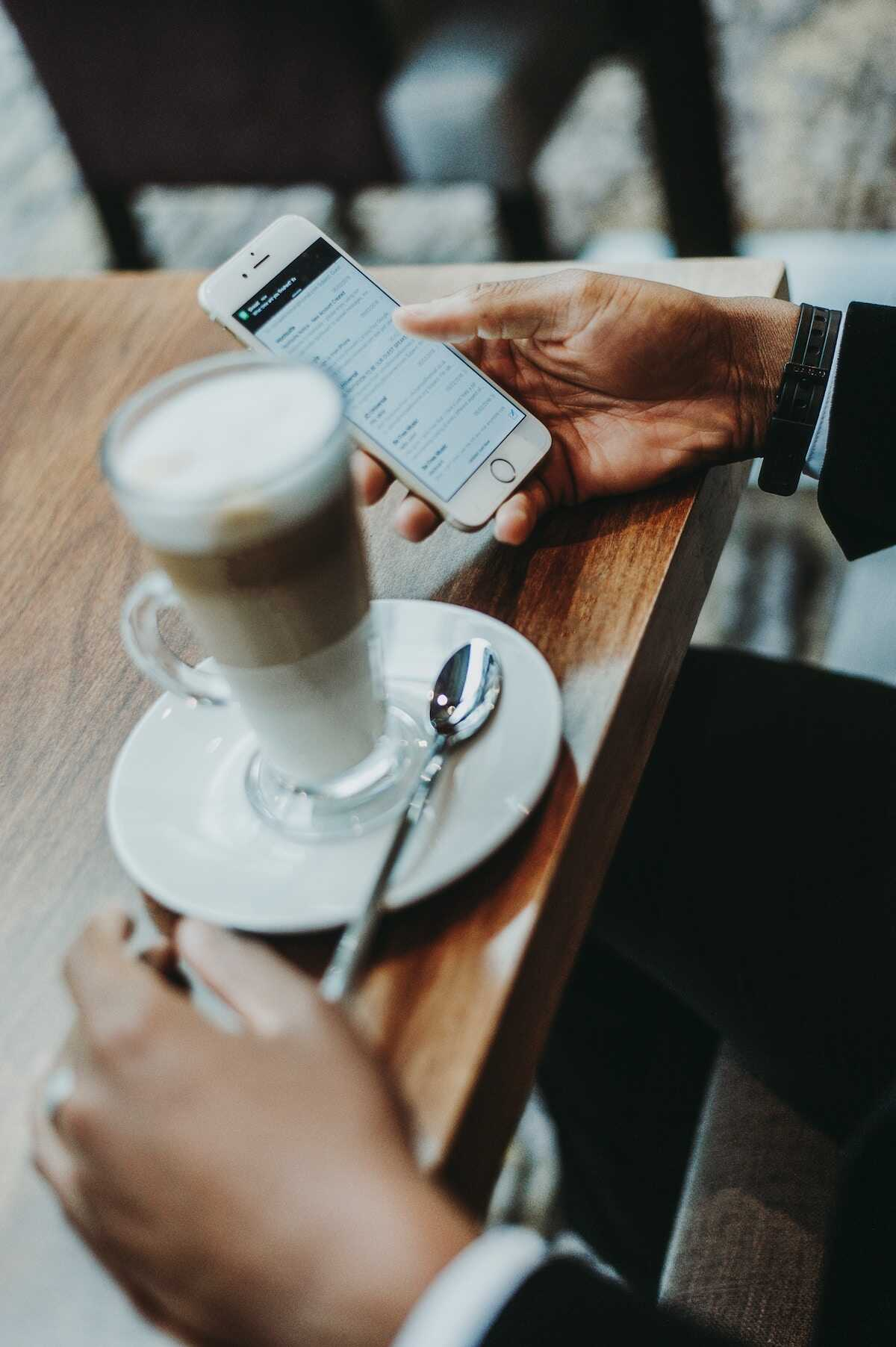Hand holding an iPhone in a coffee shop alongside a latte