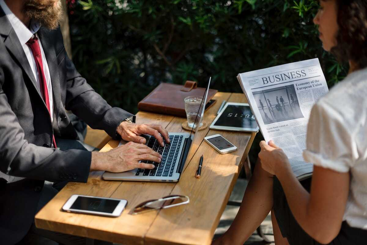 Man and woman sitting outside working and reading the business news