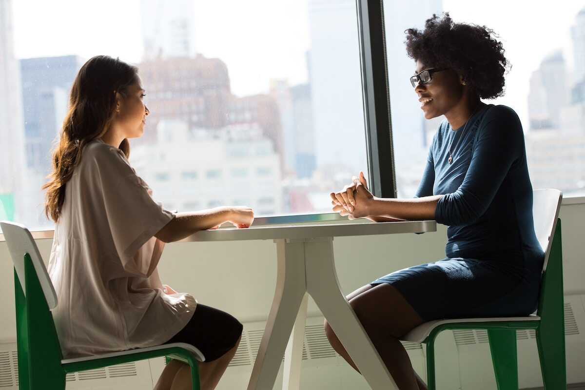 Two women sitting across from one another at a small table