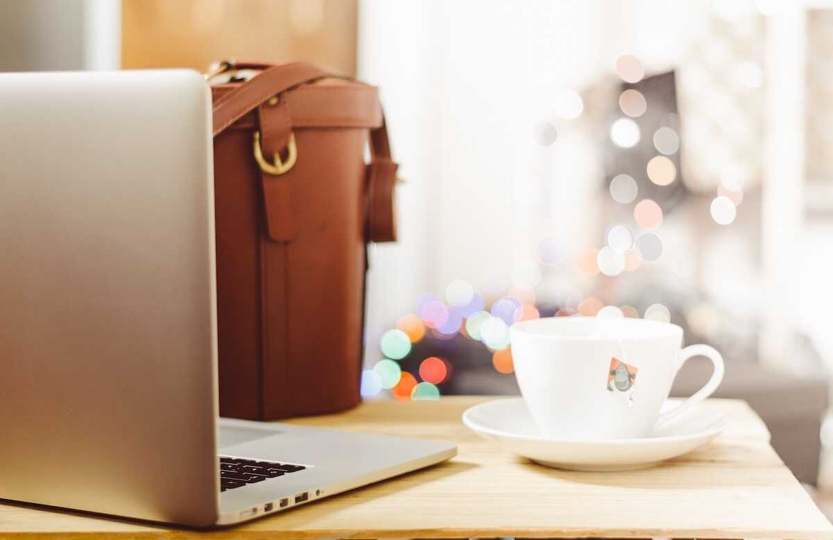 Table in a cafe featuring a laptop, cup of tea and leather bag