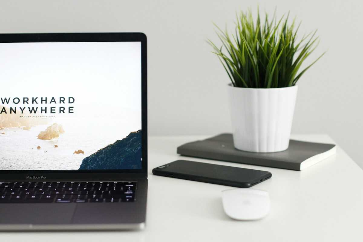 Laptop on a desk featuring the words Workhard Anywhere