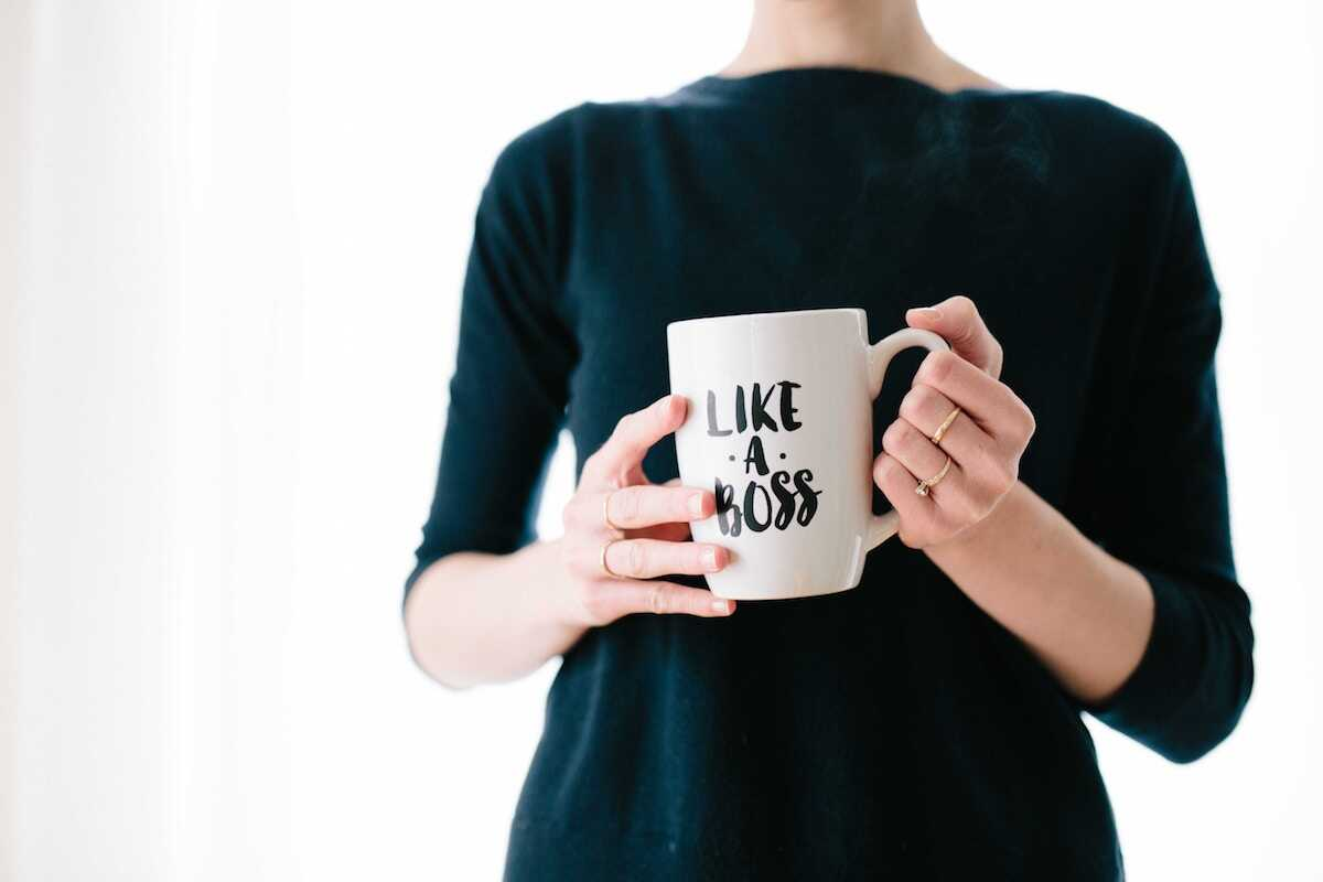Professional woman holding a white mug saying 'Like a Boss'