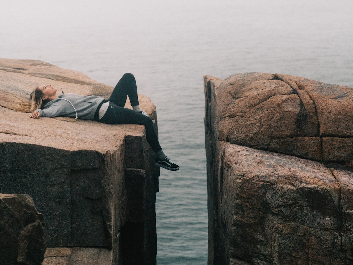 Young girl lying on a rock near in front of the sea
