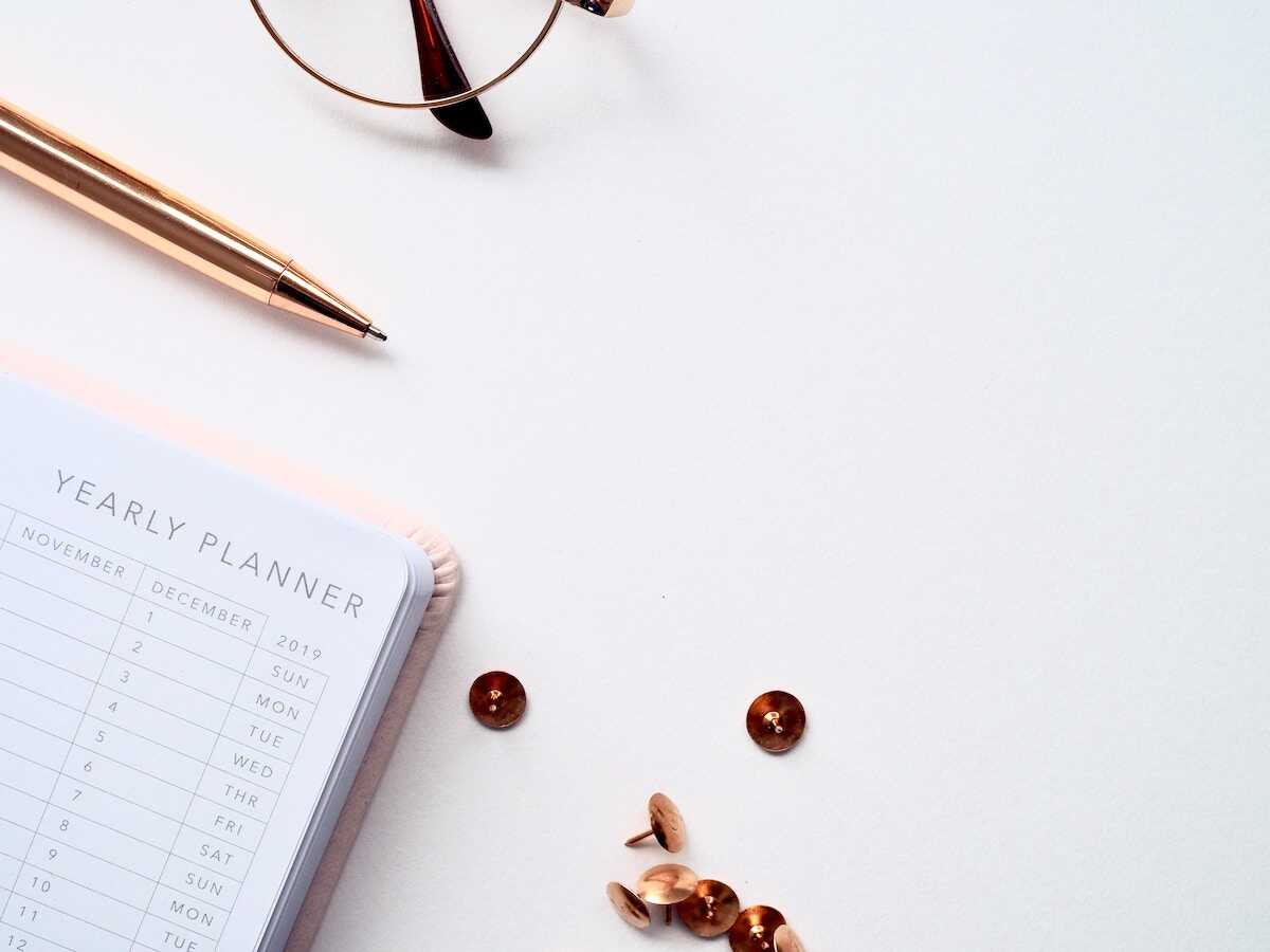 A closeup of a desk featuring a yearly planner, glasses and a pen