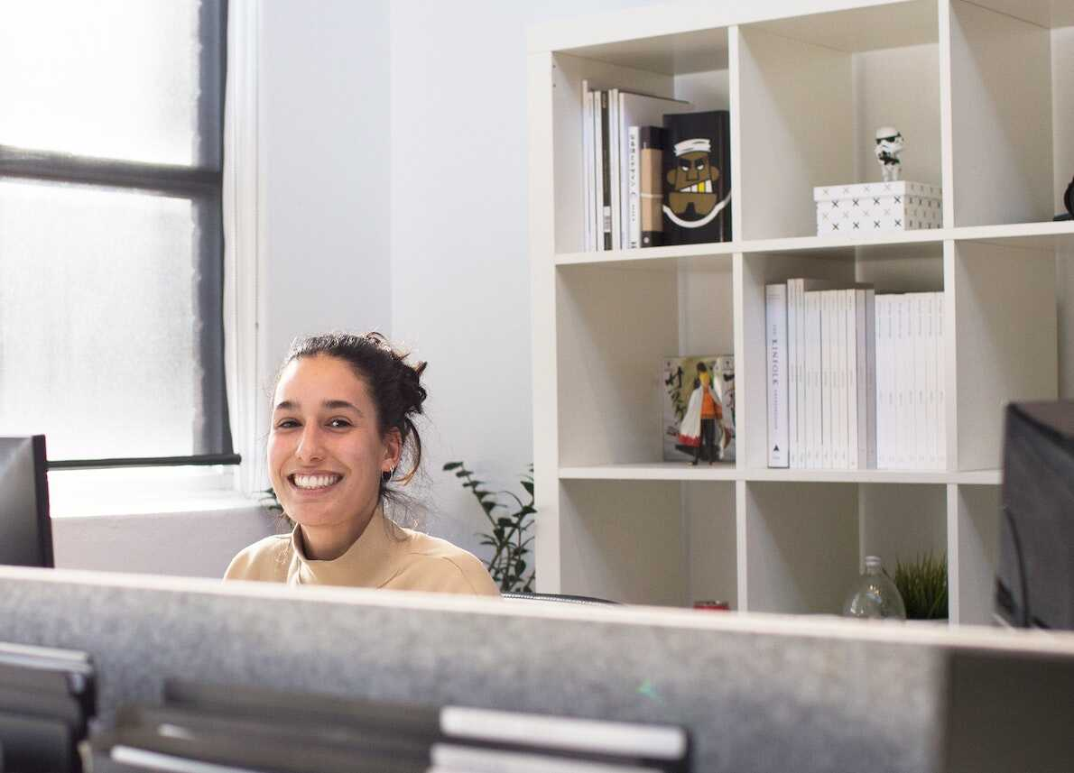 Woman smiling at work from behind her computer