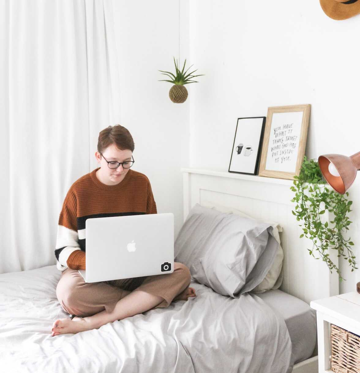 Student sitting on her bed in front of her laptop