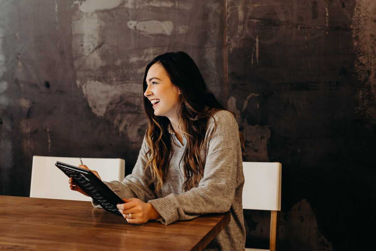 Woman smiling at a meeting room desk holding a tablet