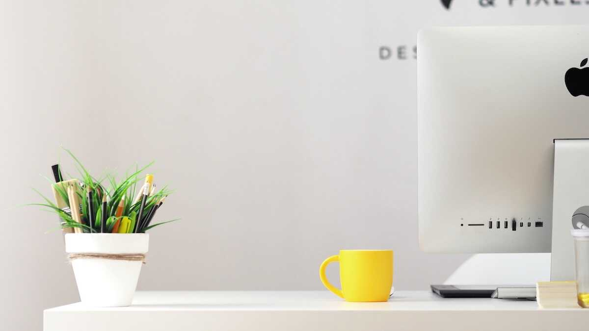 Desk featuring an iMac, yellow mug and white pen pot