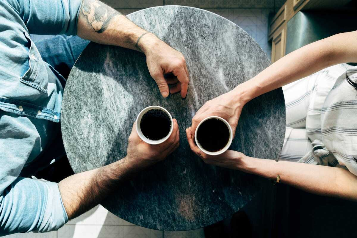 Two sets of hands holding cups of black coffee