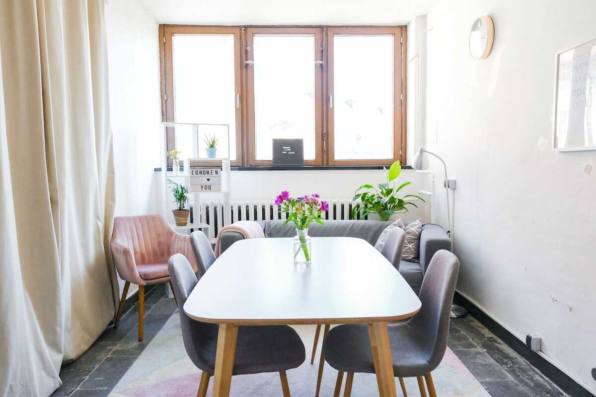 Feminine coworking space featuring a table, chairs and grey sofa