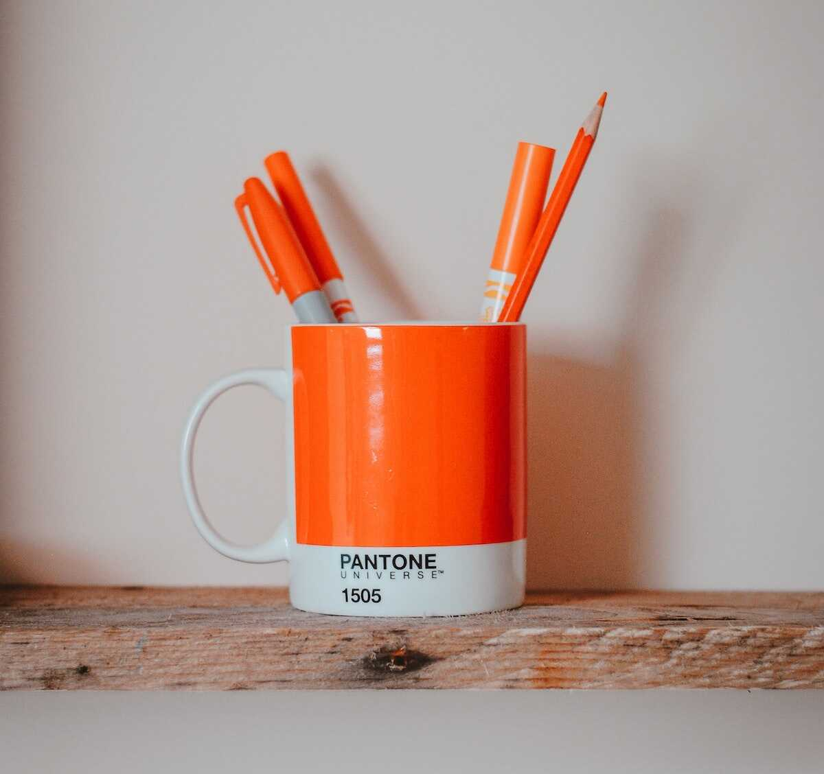 Orange pantone mug holding orange pens and pencils